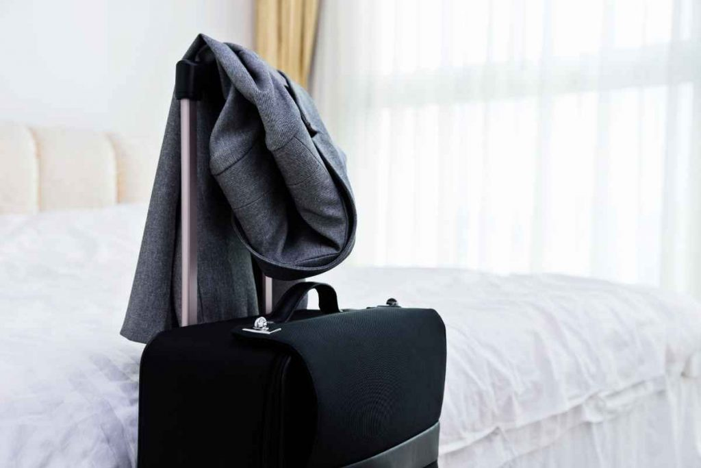 A luggage bag with a coat over it