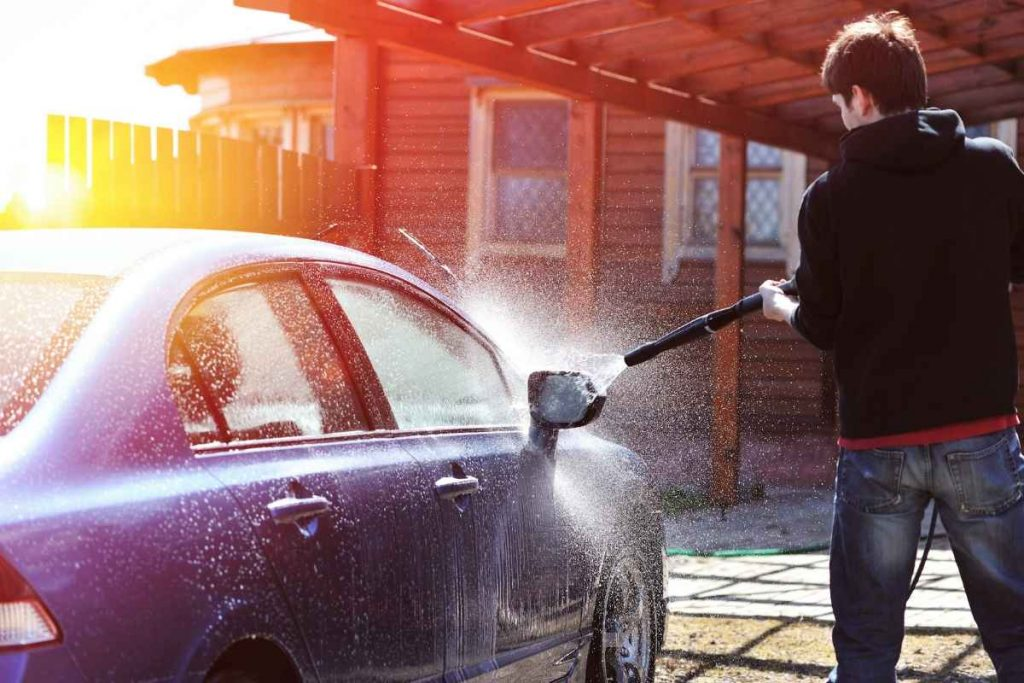 man washing the car with electrical pressure washer