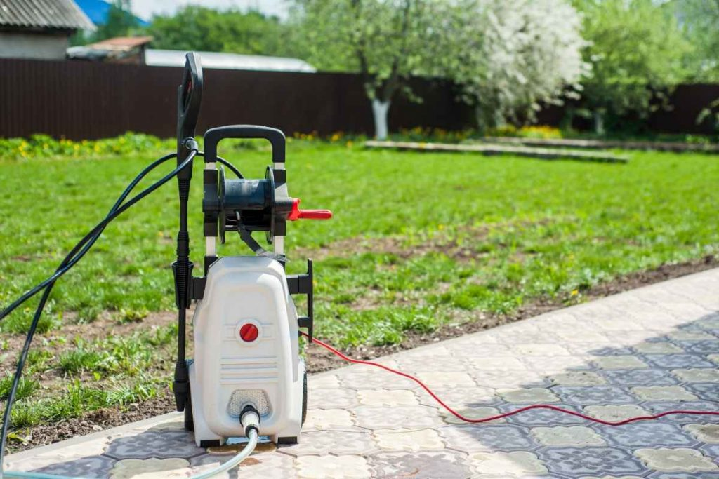 Electric pressure washer laying on a path inside plot