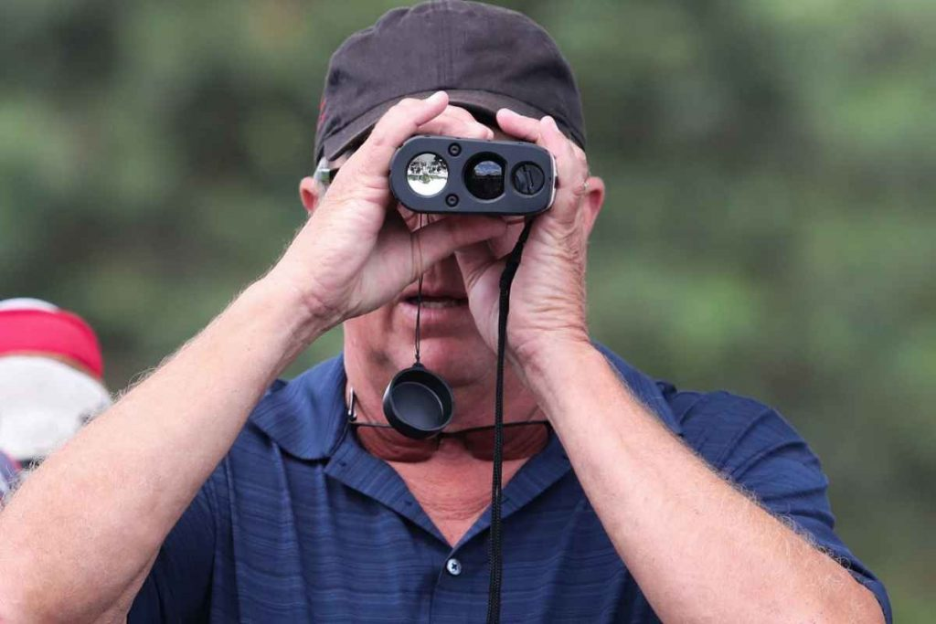 A man looking into the golf range finder