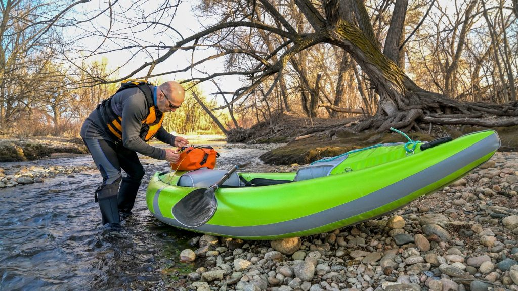A man packing a waterproof duffel bag on inflatable fishing kayaks