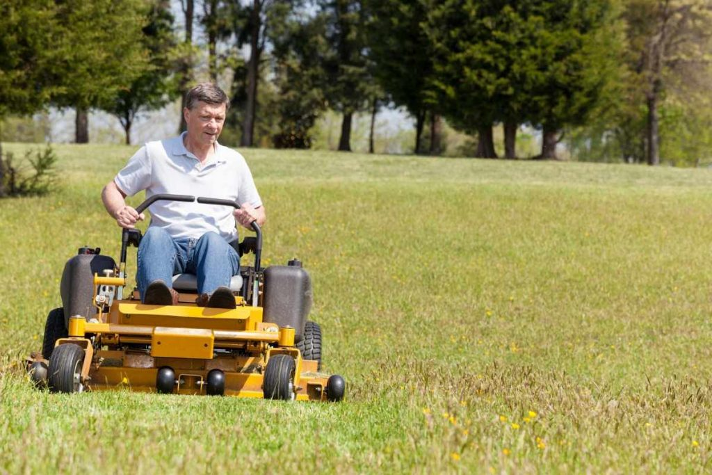 A man driving the zero turn mover on rough grass