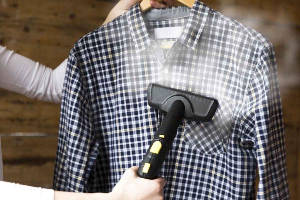 A man is using garment steamer on a shirt