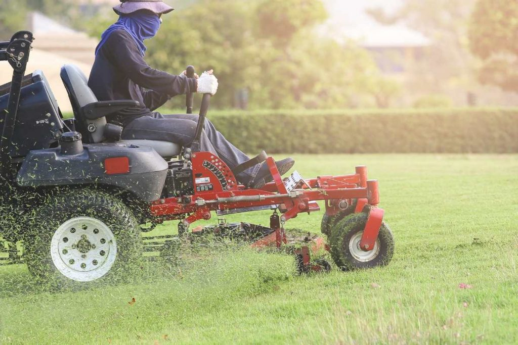 A man driving law mower on green grass