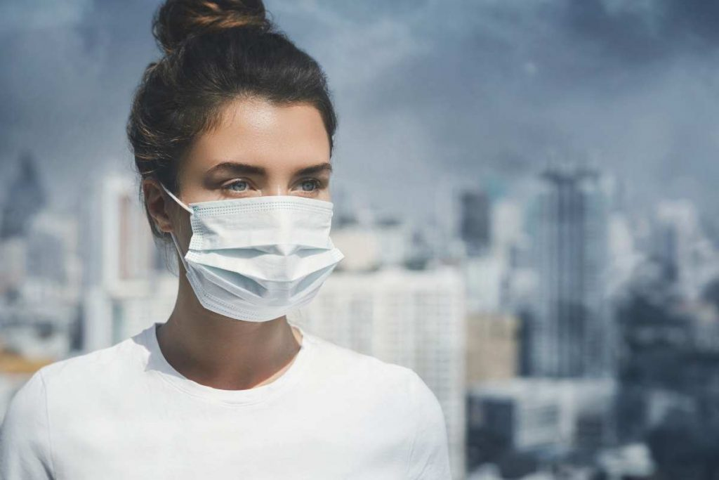 A girl wearing the mask on her mouth to avoid dust particles.