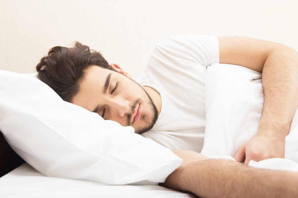 A man sleeping having a cooling pillow.