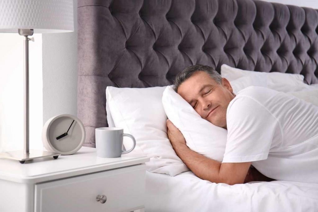 A man having rest on a comfortable bed and with cooling pillow