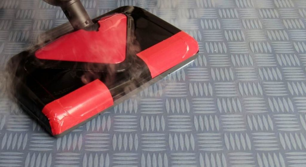 Steam cleaner working on floor to clean it.