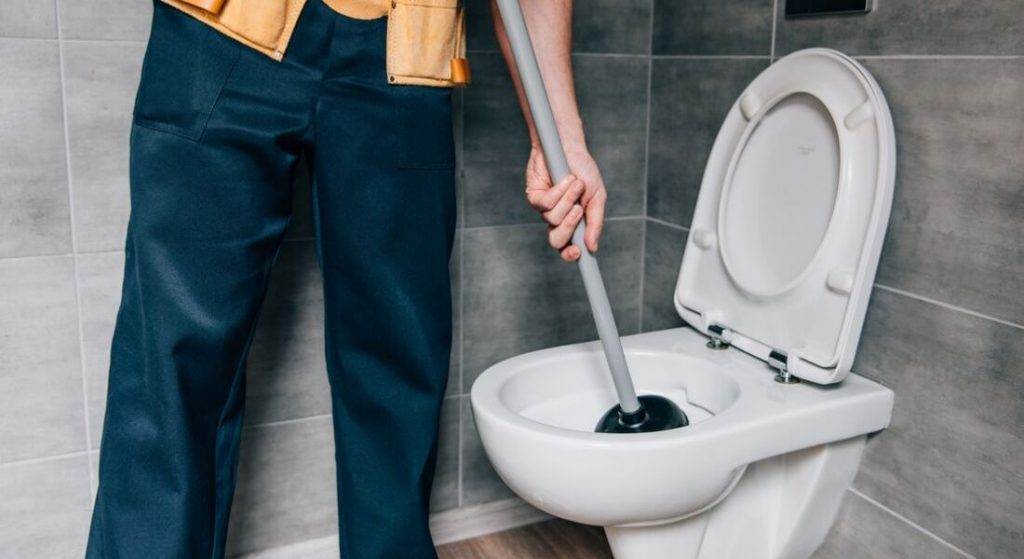 A Man using toilet plunger in commode