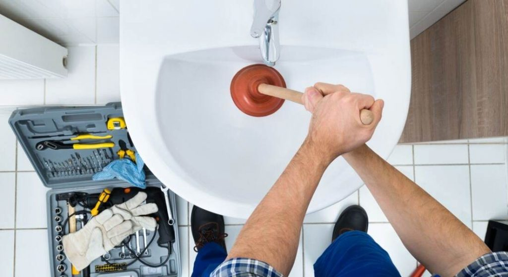 A man using toilet plunger in basin