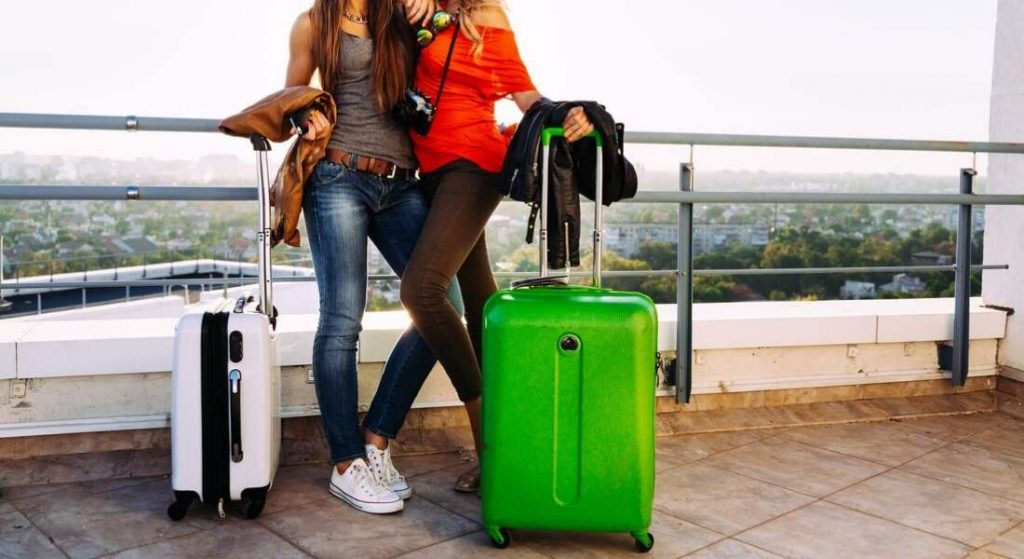 Two girls standing with luggage bag each inside
