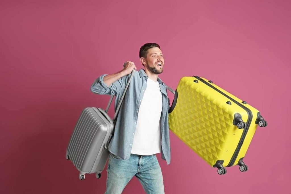 A smiling man carrying two luggage bagsl