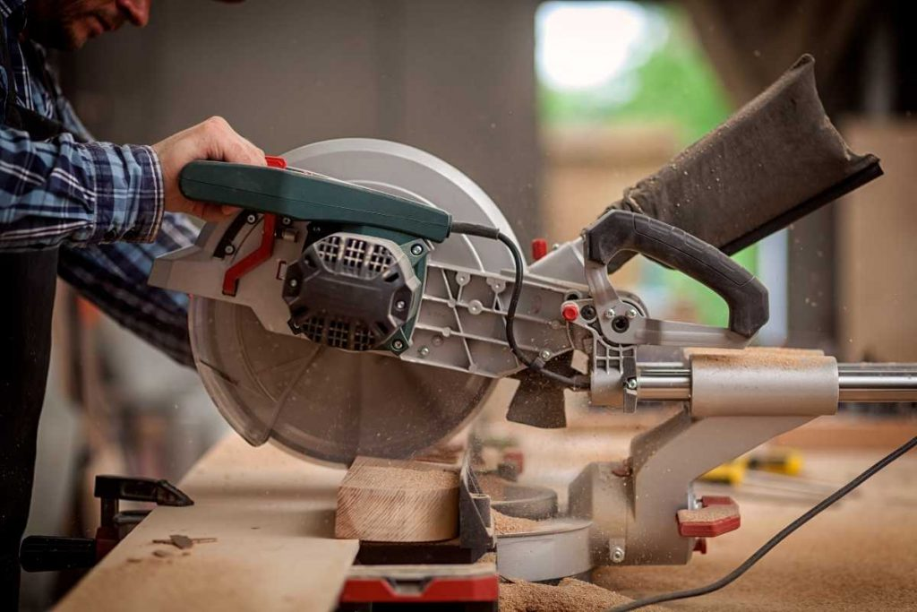 A man is cutting the wood with miter saw.