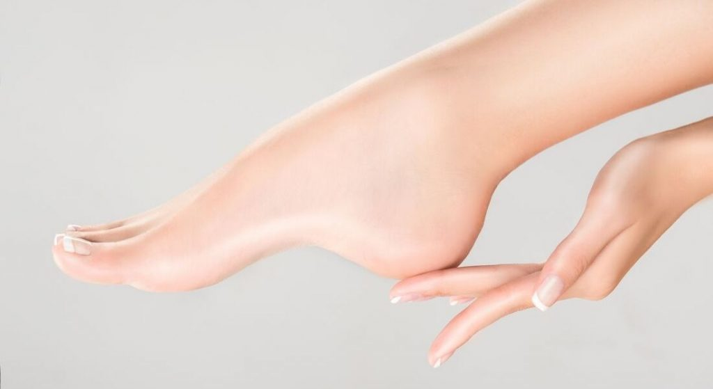 A girl touching her smooth heel with hand